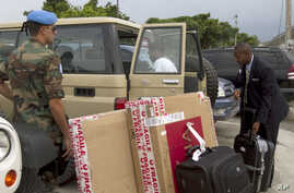 FILE - Watched by a Uruguayan peacekeepers (L) a 19-year-old man (R) who claims he was sexually abused by other Uruguayan peacekeepers, picks up his luggage from a vehicle upon his arrival to the Toussaint Louverture airport, Haiti, May 8, 2012.