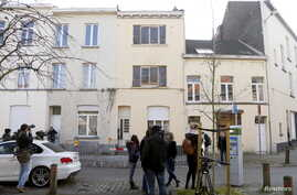 Reporters stand in front of an apartment (C) in the Brussels district of Forest where a gunman was shot dead by Belgian police on Tuesday after a raid on the apartment linked to investigations into November's Islamist attacks in Paris, March 16, 2016