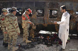 Security officials collect evidence near a damaged passenger carriage at the site of a bomb blast in the town of Sibi, Paksitan, April 8, 2014.