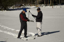 Frank Gehrke, right, Chief of California Cooperative Snow Surveys Program measures the snowpack in California's Sierra Nevada Mountains. (California Dept. of Water Resources)
