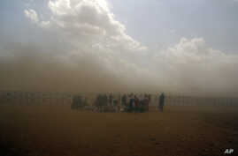 Syrian refugees enter Turkey during a sand storm at Yumurtalik crossing gate near Suruc, Turkey, Sept. 24, 2014.