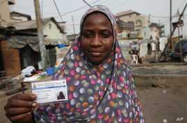 Fatima Bello display her new voters registration card in Lagos, Nigeria, Saturday, Jan. 15, 2011. An effort to register 70 million voters across Nigeria wobbled to life Saturday, as volunteers spread out across Africa's most populous nation ahead of