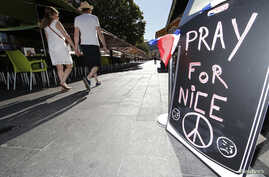 """A couple walk through the empty flower market in the old city and near a sign which reads, """"Pray for Nice"""" days after a truck attack on the Promenade des Anglais on Bastille Day killed scores and injured as many in Nice, France, July 17, 2016."""