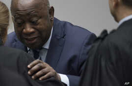 Former Ivory Coast President Laurent Gbagbo greets his legal team as he enters the courtroom of the International Criminal Court in The Hague, Netherlands, Jan. 15, 2019, where judges acquitted Gbagbo and ex-government minister Charles Ble Goude for