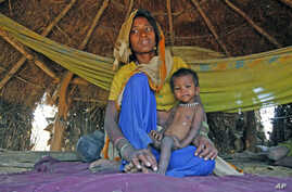 21-month-old Sushila, who weighs 4.5 kg and suffers from severe malnutrition, sits in her mother's lap in Kirwara village of Sheopur district in the central Indian state of Madhya Pradesh, April 2010 (file photo)