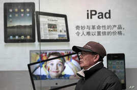A man stands near Apple's iPad advertisement in Shanghai, China, Jan. 26, 2011