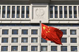 FILE - A Chinese national flag billows in front of a building of Shandong Province Supreme People's Court in Jinan, in eastern China's Shandong province, Oct. 24, 2013. Activists are calling on U.S. officials to put more focus on human rights in bila