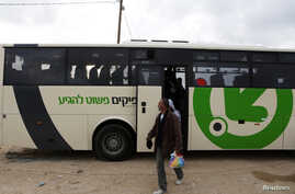 FILE - Laborers disembark a Palestinians-only bus before crossing through Israel's Eyal checkpoint as they returns to the West Bank, near Qalqilya.