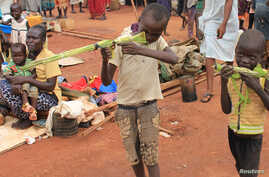 Martin Andrea, 10, and a friend play with toy guns made from long grass reeds at a displaced persons camp protected by U.N. peacekeepers in Wau, South Sudan, Sept. 4, 2016.
