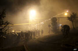 Riot police use light grenades as they confront anti-government protesters, supporters of an armed group who have been holed up inside a police station, in Yerevan, Armenia, July 29, 2016.