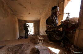 FILE - Kurdish People's Protection Units (YPG) fighters take up positions inside a damaged building in al-Vilat al-Homor neighborhood in Hasaka city, Syria.