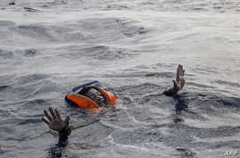 A migrant tries to board a boat of the German NGO Sea-Watch in the Mediterranean Sea, Nov. 6, 2017.