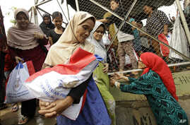 FILE - Indonesian women carry free food packages received from Indonesian President Joko Widodo during Ramadan in Jakarta, Indonesia, June 29, 2016.