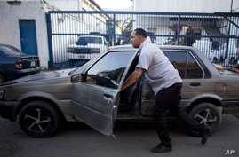 File - In this  Aug. 6, 2015 photo, taxi driver Michael Villegas pushes his car to keep his place in a line of drivers waiting to buy new car batteries in Caracas, Venezuela. Drivers faced a gasoline shortage a week ago in the South American OPEC nat