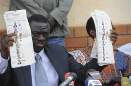 Forum for Democratic Change opposition leader Dr. Kizza Besigye displays pre-marked ballot papers, during a news conference at party headquarters in Kampala Uganda, February 19, 2011