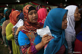Villagers line up to vote in the country's presidential election at Bojong Koneng polling station in Bogor, Indonesia, July 9, 2014.