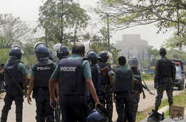 Bangladeshi policemen watch as paramilitary soldiers try to flush out Islamist radicals who have holed up in a building with a large cache of ammunition in the city of Sylhet, March 26, 2017.