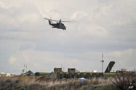 """FILE - A Russian helicopter flies on patrol while air defense missile systems are below, at Hemeimeem airbase in Syria, Jan. 20, 2016. А Russian military official dismissed as """"propaganda"""" claims by the Islamic State group that it successfully attack"""