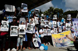 "Nicaraguan expats living in Costa Rica hold pictures of people killed in riots or imprisoned as they take part in the ""Caravan for Liberty and Justice"" to protest against the government of Nicaraguan President Daniel Ortega, in La Cruz, Costa Rica, o"