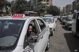 FILE - A taxi driver waits in line for fuel at a gas station, Cairo, Egypt, Sept. 4 2014.
