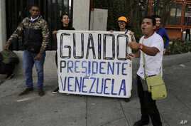 """Anti-government protesters show a sign reading in Spanish """"Guaido President of Venezuela"""" after a rally demanding the resignation of President Nicolas Maduro in Caracas, Venezuela, Jan. 23, 2019."""