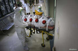 Health workers in protective suits transport a mock patient to a quarantine ward during a drill to demonstrate procedures for handling Ebola victims at a hospital in Guangzhou, China Oct. 16, 2014.