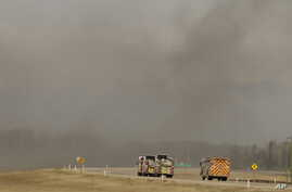 "Fire trucks drive toward smoke from a wildfire near Fort McMurray, Alberta, Canada, May 8, 2016.  Officials said Sunday they were hoping to get a ""death grip"" on the blaze amid cooler temperatures."