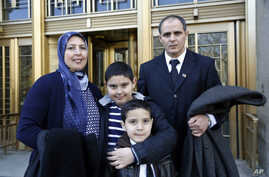 Nezha and Mohamed Hariz, from left, pose with sons Nassim, 9, and Mouad, 7, outside a federal courthouse where they became U.S. citizens, March 18, 2016. The New York state family is from Morocco.