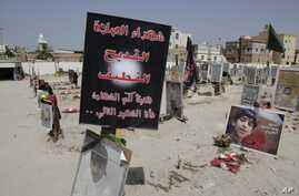 FILE- Religious flags, photographs and tributes to 21 victims of a suicide bombing, claimed by the Islamic State group, of a Shi'ite mosque are seen attached to their graves at a cemetery in Qudeeh, Saudi Arabia, May 30, 2015.