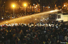 Police use water cannons to disperse demonstrators as they protest against a trade pact with mainland China, near Taiwan's government headquarters in Taipei, early morning, March 24, 2014.