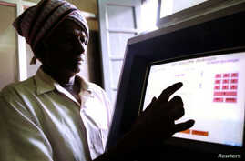 FILE - An Indian farmer uses a computer to check land-records in the village of Ramanagaram 40 km (25 miles) in the southern Indian state of Karnataka, May 26, 2001.