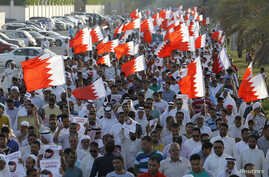 Protesters holding Bahraini flags march during anti-government protest organised by country's Al Wefaq opposition party, Budaiya, west of Manama, June 6, 2014.