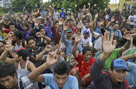 FILE - In this April 3, 2015 photo, rescued Burmese fishermen raise their hands as they are asked who among them wants to go home at the compound of Pusaka Benjina Resources fishing company in Benjina, Aru Islands, Indonesia. Two Indonesians and five