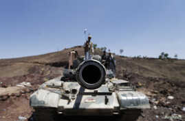 A frontal view of a tank barrel is seen as Shi'ite Houthi rebels stand on its turret, after they took over the compound of the army's First Armored Division in Sana'a, Yemen, Sept. 22, 2014.