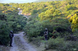 Mexican marines guard the area where new clandestine mass graves were found on the ouskisrts of Cocula, Mexico, Oct. 27, 2014.
