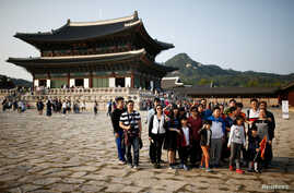 Chinese tourists pose for a group photo at the Gyeongbok Palace in central Seoul, South Korea, Oct. 5, 2016. About 8 million Chinese tourists have visited South Korea in the last five years.