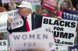 """Campaign 2016 Trump: Republican presidential candidate Donald Trump kisses a """"Women for Trump"""" sign during a campaign rally, Wednesday, Oct. 12, 2016, in Lakeland, Florida."""