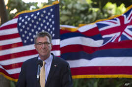 With the U.S. and Hawaii flags fluttering in the background, Defense Secretary Ash Carter speaks at a press conference during a defense ministers meeting of ASEAN, in Kapolei, Hawaii, Sept. 30, 2016.