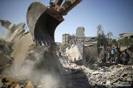Palestinians gather as  rescue workers search for victims from under the rubble of a house, which witnesses said was destroyed by an Israeli airstrike, in Beit Lahiya, northern Gaza Strip, Aug. 25, 2014.