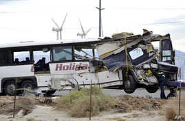 Workers prepare to haul away a tour bus that crashed with semi-truck on Interstate 10 just west of the Indian Canyon Drive off-ramp, in Desert Hot Springs, near Palm Springs, California, Oct. 23, 2016.