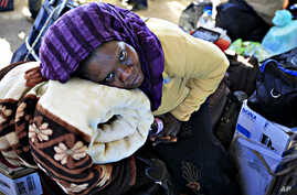A Nigerian migrant worker who fled the unrest in Libya waits at the Libyan and Tunisian border crossing of Ras Jdir, March 3, 2011