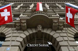 FILE - National flags of Switzerland fly over the entrance of the headquarters of Swiss bank Credit Suisse in Zurich July 31, 2014.