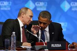 U.S. President Barack Obama (R) listens to Russia's President Vladimir Putin before the opening of the first plenary session of the G-20 Summit in Los Cabos, Mexico, June 18, 2012.