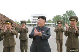 FILE - North Korean leader Kim Jong Un applauds during a photo session with soldier-builders of KPA Units 966, 462, 101, 489.