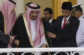 Indonesian President Joko Widodo, right, assists Saudi King Salman, center, to walk during their meeting at the presidential palace in Bogor, West Java, Indonesia, Wednesday, March 1, 2017.
