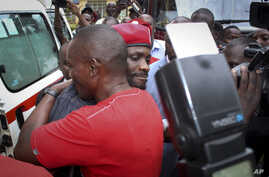 Ugandan pop star Kyagulanyi Ssentamu, better known as Bobi Wine, center, wears a beret and is hugged by a supporter as he gets into an ambulance after leaving the courthouse in Gulu, Uganda, Aug. 27, 2018.