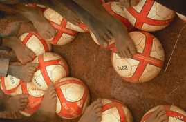 Children in Benin get a foot on their new soccer balls from Project Play Africa in 2010. (Courtesy Project Play Africa)