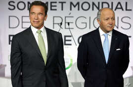 Former governor of California and founding chair of the R20 initiative, Arnold Schwarzenegger, left, and France's Foreign Minister Laurent Fabius, stand prior to making a speech at the World Summit of Regions for Climate, in Paris, Oct. 11, 2014.