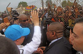 Photo taken April 5, 2014, 2014 shows U.N. Secretary-General Ban Ki-moon, in a cap, waving at people kept back by a wire fence, as he walks surrounded by U.N. security personnel in a secured location in Bangui, Central African Republic.