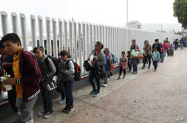 FILE - People line up to cross into the United States to begin the process of applying for asylum near the San Ysidro port of entry in Tijuana, Mexico, July 26, 2018.
